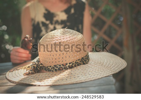 A young woman is sitting at a table with a big straw hat in front of her
