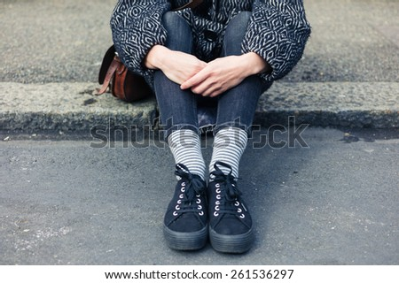 A young woman is sitting in the street on the curb