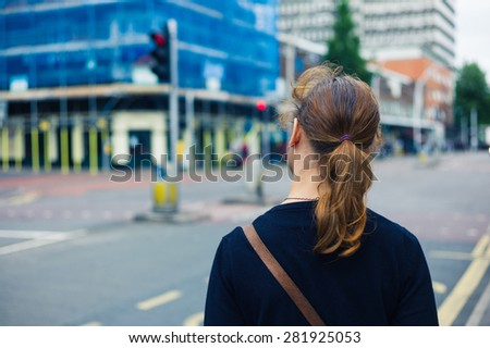 A young woman is standing in the street