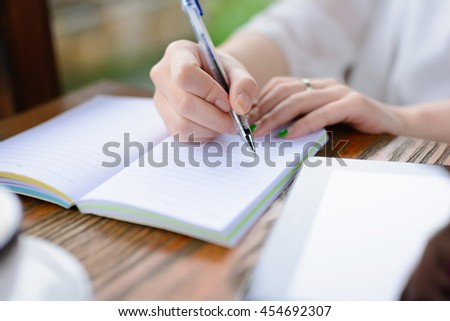 A young woman is writing .