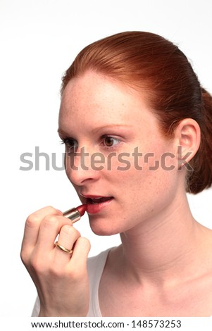 A young woman putting on lipstick.