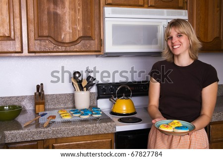 a young woman showing you the cookies she has baked