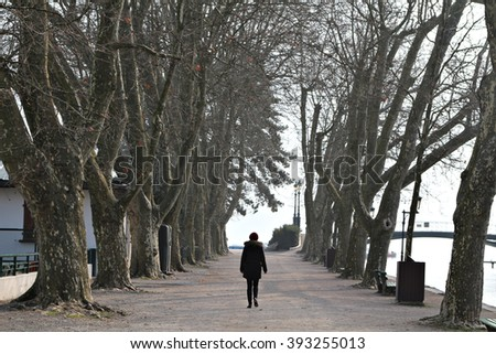 A young woman walks down a tree-lined walkway, street or path.