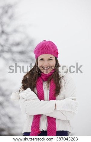 A young woman wearing a pink hat and scarf, trying to keep warm