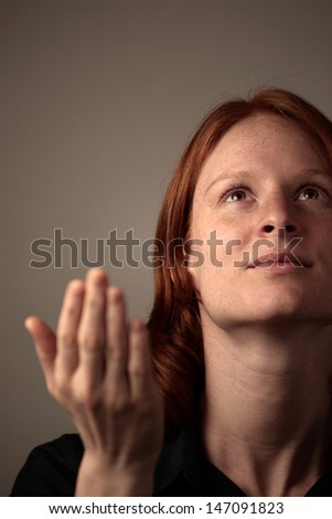 A young woman worshiping God - praying and praising. Photographed over dark background with copy space available at the top left.