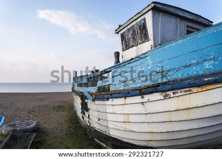 Abandoned fishing boat on beach during lovely Summer morning