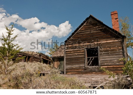 Abandoned frame house and a large log structure with a collapsed roof in a Montana ghost town