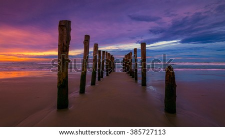 Abandoned wooden piles in St. Clair Beach in Dunedin during sunrise
