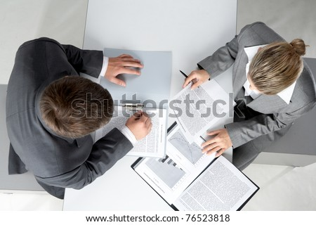 Above angle of two business partners planning work at meeting