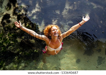 Above view of cheerful young woman raising her hands and standing in water