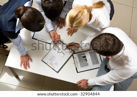 Above view of friendly workteam discussing business-plan