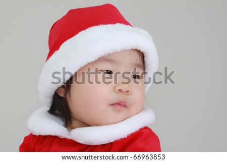 Absolutely Beautiful Young Baby Infant East Asian Girl Toddler in Red and White Santa Outfit Awaiting the opening of presents at Christmas Time during the holidays