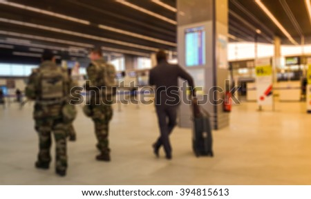 Abstract blurred background : Soldiers on patrol in airport terminal for Vigipirate Plan against terrorism in France. Airline passenger with luggage watch a flight information board. Security concept