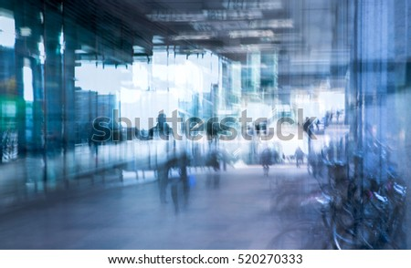 Abstract, blurred image of people walking via long tunnel with light at the background.