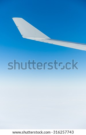 Abstract monochromatic image of a modern airplane's wing photographed against a blue sky background that grades downward into white clouds