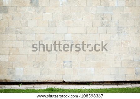 Abstract urban wall with grass and a sidewalk