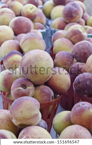 Abundance of peaches (binomial name: Prunus persica) in red baskets at a farmer's market (selective focus)