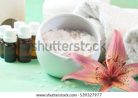 Accessories for bath - bath salt in bowl, essential oils, towels -decorated with pink lily