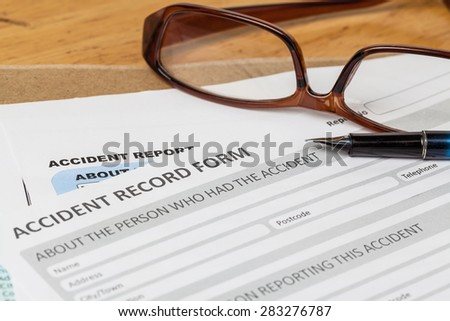 Accident report application form and pen on brown envelope and eyeglass, business insurance and risk concept; document is mock-up