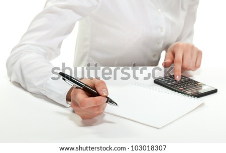 Accountant at work; female hands with calculator, pen and sheet of paper