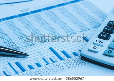 Accounting financial banking stock spreadsheet data with pen and calculator in blue