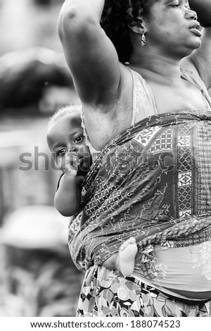 ACCRA, GHANA - MAR 4, 2012: Unidentified Ghanaian baby boy on his mother back. People of Ghana suffer of poverty due to the difficult economic situation