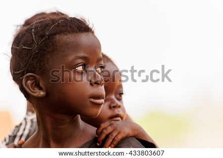 ACCRA, GHANA - MARCH 6, 2012: Unidentified Ghanaian girl and her little brother in the street in Ghana. Children of Ghana suffer of poverty due to the unstable economic situation