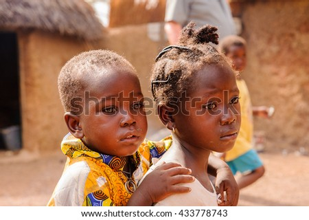 ACCRA, GHANA - MARCH 6, 2012: Unidentified Ghanaian girl carries her little brother on his back in the street in Ghana. Children of Ghana suffer of poverty due to the unstable economic situation