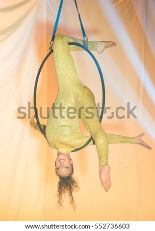 Acrobatic artist face down on the hoop, on stage