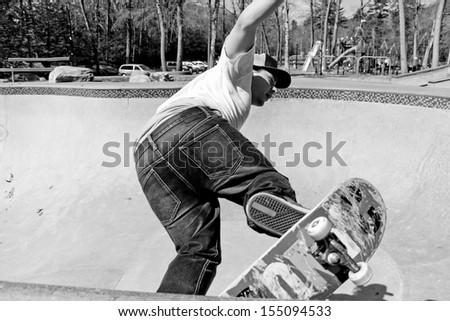 Action shot of a skateboarder skating in a concrete skateboarding bowl at the skate park. High contrast black and white.