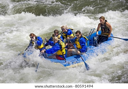 Action shot of people riding the rapids in Colorado.