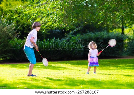 Active children playing badminton. Two happy kids, boy and girl having fun on a family picnic in a park, enjoying sport games, running and jumping with tennis racket on a hot summer day outdoors.