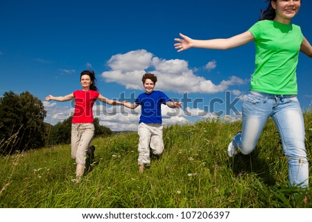 Active family - mother and kids running, jumping outdoor