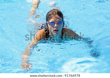 Active girl swimming in swimming pool