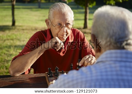 Active retired people, old friends and free time, two senior men having fun and playing chess at park. Head and shoulders