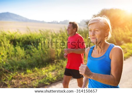 Active seniors running outside in green nature