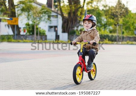 Active toddler boy having fun and riding his bike  in the city