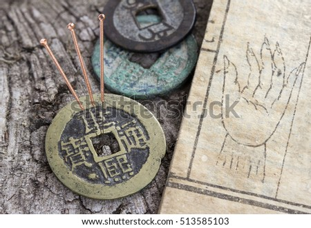 acupuncture needles beside an old medicine book and antique coins