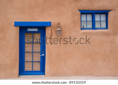Adobe house with a blue door and window