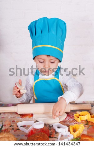 adorable baby cooking in kitchen. little cute child in costume of Cook. Pretty beautiful boy covered in flour makes cakes.baby boy