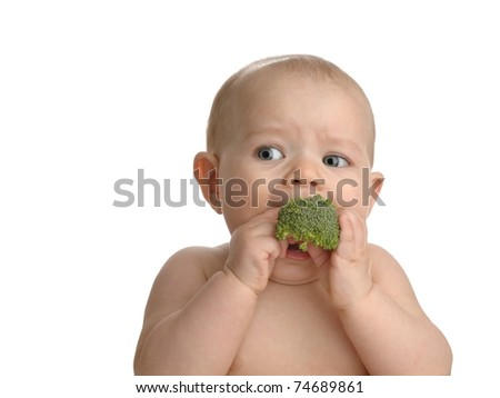 Adorable baby girl eating broccoli isolated on a white background.