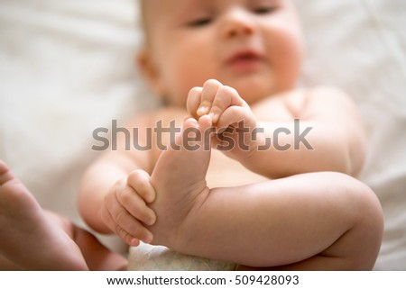 Adorable baby taking an interest in his feet, amusing himself, playtime. Closeup. Family, baby development photo. Focus on a leg