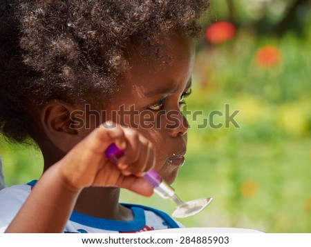 Adorable black African baby eating with food full face