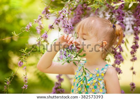 Adorable blonde girl with purple flowers