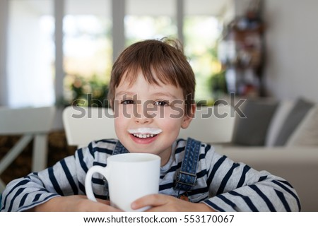 Adorable boy drinking milk or yogurt, shallow depth of field