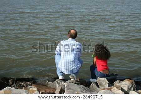 Adorable five year old African American Girl fishing with her father. Multi racial family.