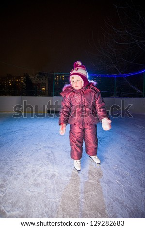 Adorable girl in skates stay on ice rink in evening