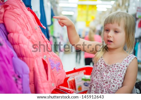 Adorable girl select winter jacket in cloth department in supermarket