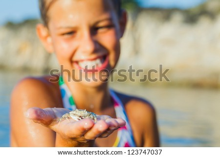 Adorable happy girl holding crab on hand on the beach. Focus on the crab.