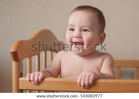 Adorable happy young baby with a lovely smile standing up in a wooden cot looking to the side gurgling with pleasure, gorgeous sentimental portrait